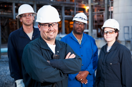 Multi-ethnic Group Of Engineers Working At A Chemical Plant.  Focus On Man (30s) In Foreground.